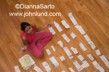 An hispanic woman is sitting on her hardwood floor surrounded by and organizing piles of receipts. She is working on her personal finance.
